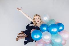 De blondevrouw met ballons viert iets Stock Fotografie