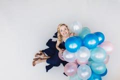 De blondevrouw met ballons viert iets Royalty-vrije Stock Fotografie