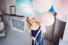 De blondevrouw met ballons viert iets Royalty-vrije Stock Afbeelding