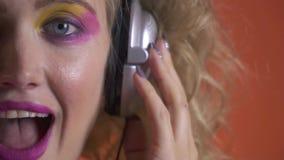 De blondevrouw met blauwe ogen, die hoofdtelefoons dragen, door de muziek worden verbaasd, sluit omhoog stock footage