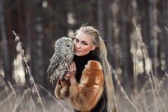 De blondevrouw met een uil in haar handen loopt in het hout in autu royalty-vrije stock foto