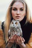 De blondevrouw met een uil in haar handen loopt in het hout in de herfst en de lente Lang haarmeisje, romantisch portret met uil royalty-vrije stock afbeelding