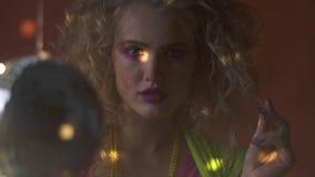 De blondevrouw met het verleiden kijkt, retro, discobal en lichten stock video