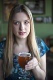 De blondevrouw met Mooie Blauwe Ogen drinkt een Drinkbeker Bier Stock Afbeelding