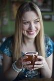 De blondevrouw met Mooie Blauwe Ogen drinkt een Drinkbeker Bier Royalty-vrije Stock Foto's
