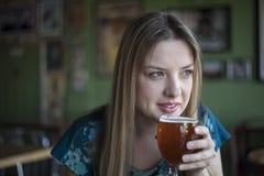 De blondevrouw met Mooie Blauwe Ogen drinkt een Drinkbeker Bier Royalty-vrije Stock Afbeeldingen