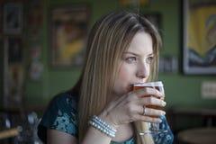 De blondevrouw met Mooie Blauwe Ogen drinkt een Drinkbeker Bier Stock Fotografie