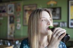 De blondevrouw met Mooie Blauwe Ogen drinkt een Fles Bier Stock Fotografie