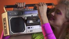 De blondevrouw met retro blik zet een cassette in de uitstekende bandrecorder stock video