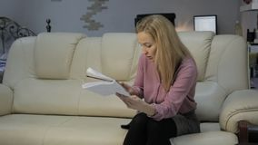 De blondevrouw op een bank leest haar nota's in een notitieboekje en controleert nota's met smartphone stock footage