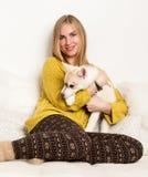 De blondevrouw in pyjama's en wollen sokken met schor puppy ligt op een wit bed royalty-vrije stock foto