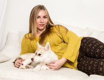 De blondevrouw in pyjama's en wollen sokken met schor puppy ligt op een wit bed royalty-vrije stock afbeeldingen