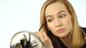 De blondevrouw schildert haar wimpers en het doen van dagelijkse make-up met borstel voor kleine spiegel 4K stock video