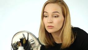 De blondevrouw schildert haar wimpers en het doen van dagelijkse make-up met borstel voor kleine spiegel Langzame Motie stock video