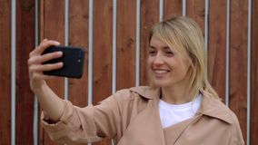 De blondevrouw spreekt in openlucht door videogesprek op haar smartphone stock video