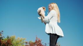 De blondevrouw stuitert hoog omhoog tegen de hemel, houdt een puppy in haar handen 4K video stock video