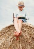 De blootvoetse jongen leest een boek op de bovenkant van hooiberg zit royalty-vrije stock foto's
