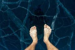De blootvoetse mannelijke voeten bevinden zich op het blauwe ijs van Meer Baikal, in barsten stock fotografie