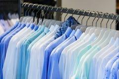 De blouses van vrouwenoverhemden op een klerenrek stock foto's