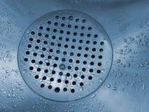 De bodem van een gootsteen met water wordt gevuld dat daalt stock fotografie