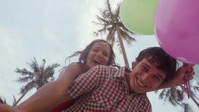 De bodemmening van gelukkig meisje op de schouders van de haar mens houdt ballons die pret op palmen op de achtergrond hebben A stock footage