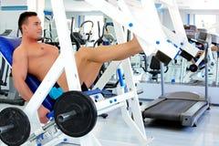 De bodybuilder doet beenpersen Stock Fotografie