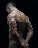 De bodybuilder en de strook als thema hebben: mooi met het gepompte spieren naakte mens stellen in de studio op een donkere achte royalty-vrije stock afbeeldingen