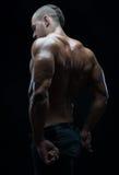 De bodybuilder en de strook als thema hebben: mooi met het gepompte spieren naakte mens stellen in de studio op een donkere achte royalty-vrije stock fotografie