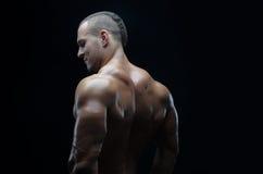 De bodybuilder en de strook als thema hebben: mooi met het gepompte spieren naakte mens stellen in de studio op een donkere achte royalty-vrije stock foto