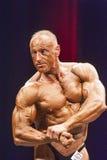 De bodybuilder toont de borst op stadium in kampioenschap stelt Stock Afbeelding