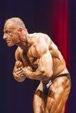 De bodybuilder toont het meest spier op stadium in kampioenschap stel Stock Afbeeldingen