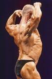 De bodybuilder toont terug spier op stadium in kampioenschap Stock Foto's