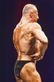 De bodybuilder toont terug zijn spier op stadium in kampioenschap Stock Foto's