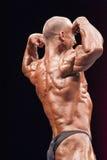 De bodybuilder toont zijn beste achter dubbele bicepsen stellen Stock Fotografie