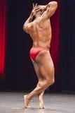 De bodybuilder toont zijn beste lichaamsbouw op stadium Stock Fotografie