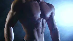 De bodybuilder toont zijn lichaam, sterkte en duurzaamheid aan Zwarte rookachtergrond Langzame Motie stock videobeelden