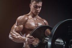 De bodybuilder treft voorbereidingen om oefeningen met barbell te doen royalty-vrije stock foto
