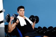 De bodybuilder werkt met gewichten uit Stock Foto's