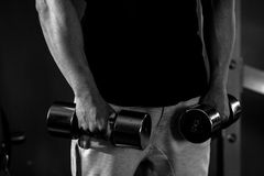 De bodybuilderkerel in gymnastiek met geschiktheidsdomoren overhandigt dicht op mon Stock Afbeeldingen