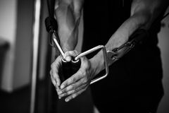 De bodybuilderkerel in gymnastiek overhandigt dicht omhoog stock foto's