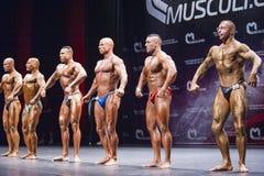De bodybuilders tonen hun lichaamsbouw op stadium in kampioenschap Stock Fotografie