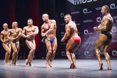 De bodybuilders tonen hun lichaamsbouw op stadium in kampioenschap Stock Foto