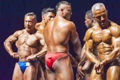 De bodybuilders tonen hun lichaamsbouw op stadium in kampioenschap Royalty-vrije Stock Afbeelding