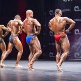De bodybuilders tonen hun lichaamsbouw op stadium in kampioenschap Royalty-vrije Stock Foto's
