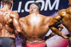 De bodybuilders tonen hun lichaamsbouw op stadium in kampioenschap Royalty-vrije Stock Afbeeldingen