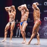 De bodybuilders tonen hun lichaamsbouw op stadium in kampioenschap Royalty-vrije Stock Fotografie