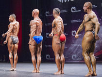 De bodybuilders tonen hun lichaamsbouw op stadium in kampioenschap Stock Afbeeldingen