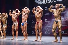 De bodybuilders tonen hun lichaamsbouw op stadium in kampioenschap Stock Foto's