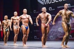 De bodybuilders tonen hun lichaamsbouw op stadium in kampioenschap Royalty-vrije Stock Foto
