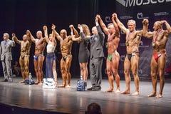 De bodybuilders vieren hun overwinning op stadium met ambtenaren Royalty-vrije Stock Fotografie